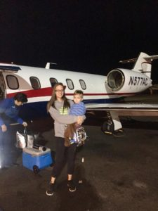 Jaxson and his mom standing beside plane image