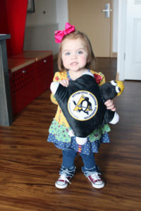 Lilah smiling holding a Pittsburgh Penguins pillow image